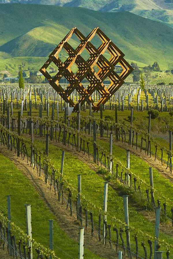 Geometrische Skulptur ragt über Weinreben